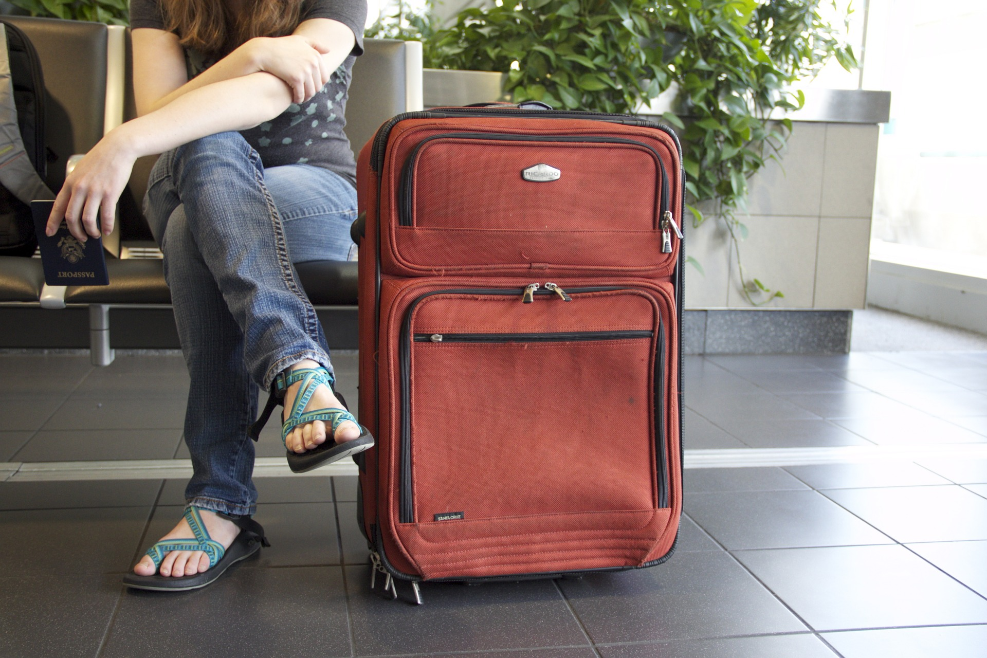 a girl on a suitcase - Travel Guide: Backpack Vs Suitcase